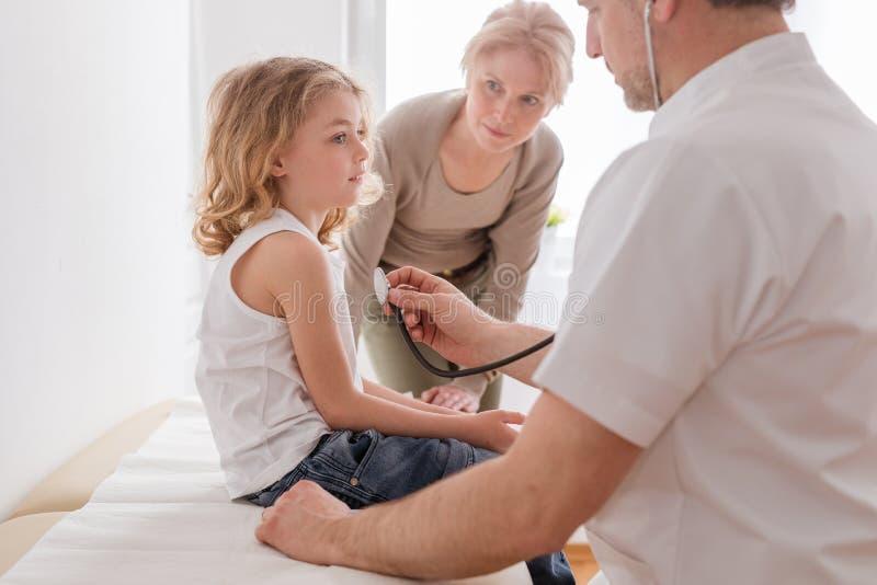 审查有肺炎的儿科医生逗人喜爱的男孩,在他们后的担心的母亲 免版税图库摄影