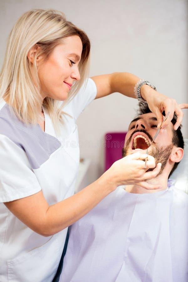 审查牙齿诊所的美丽的年轻女性牙医年轻男性患者 库存图片