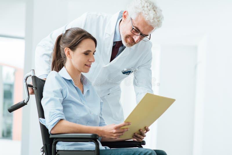 审查病历的医生和患者 免版税库存图片