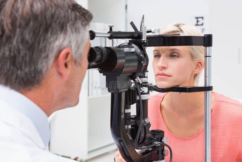 审查白肤金发的妇女的验光师 免版税库存照片
