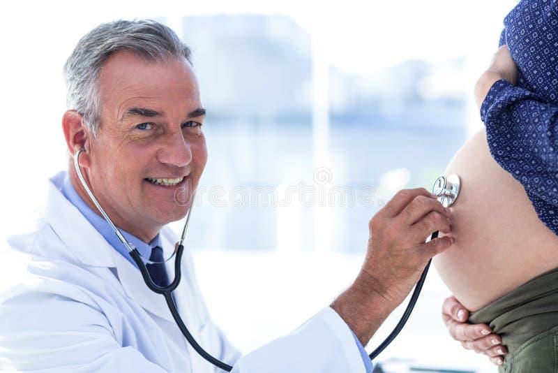 审查诊所的男性医生画象孕妇 库存照片