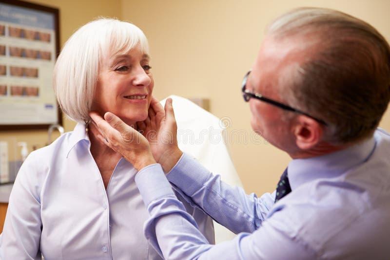 审查资深女性客户的整容外科医生  图库摄影