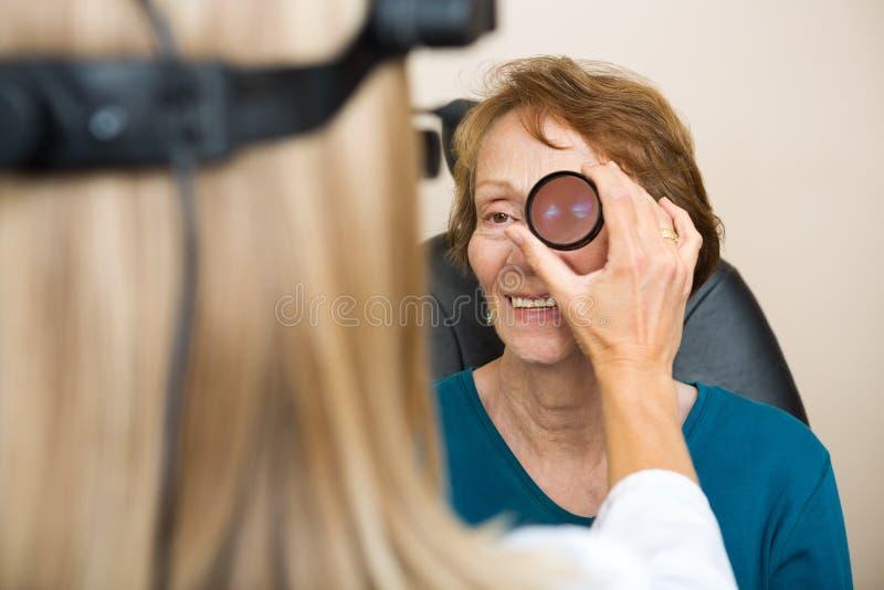审查资深妇女的眼睛的眼镜师 库存照片