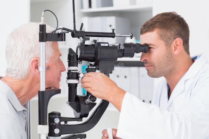 审查资深患者的验光师通过被切开的灯注视 免版税图库摄影