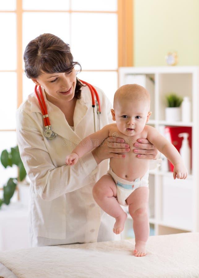 审查逗人喜爱的男婴的儿科医生 医生测试走的反射 库存图片