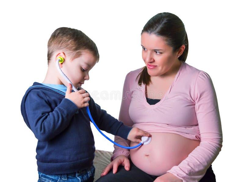审查他怀孕的母亲的儿童医生 免版税库存图片