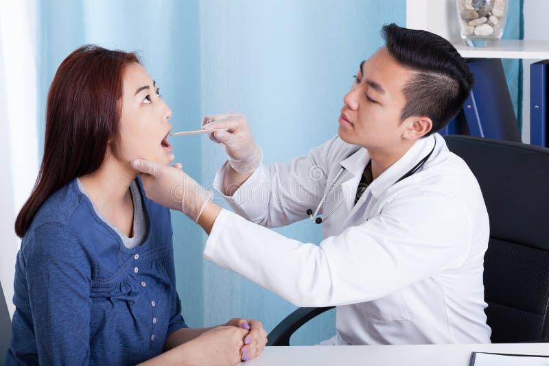 审查他的女性患者的亚裔医生 免版税库存照片