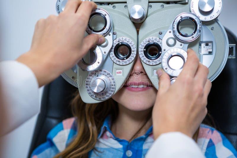审查phoropter的女性验光师年轻患者 库存照片