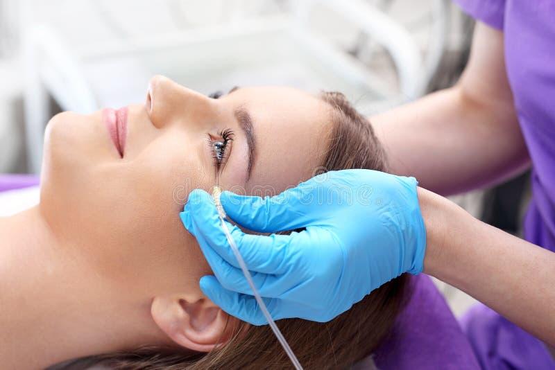 审美医学的医生执行一种面部皮肤刮的治疗与注射器 库存照片