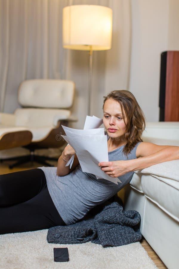 审阅一些文书工作的俏丽,少妇在她可爱的客厅在晚上 库存图片