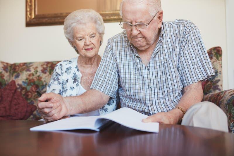 审阅一些退休文书工作的成熟夫妇 免版税库存图片