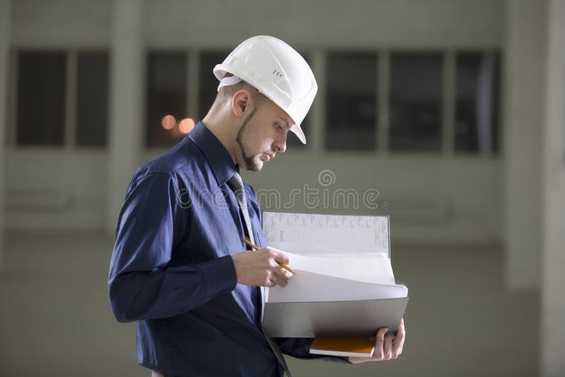 审阅文件夹的建筑师在仓库里 库存照片