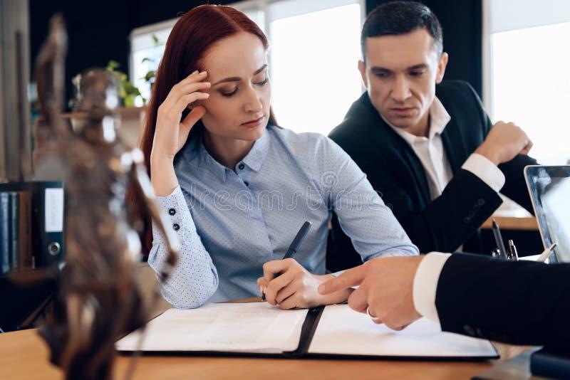审阅离婚签署的纸的夫妇 成人丈夫和妻子签署离婚解决 免版税库存照片
