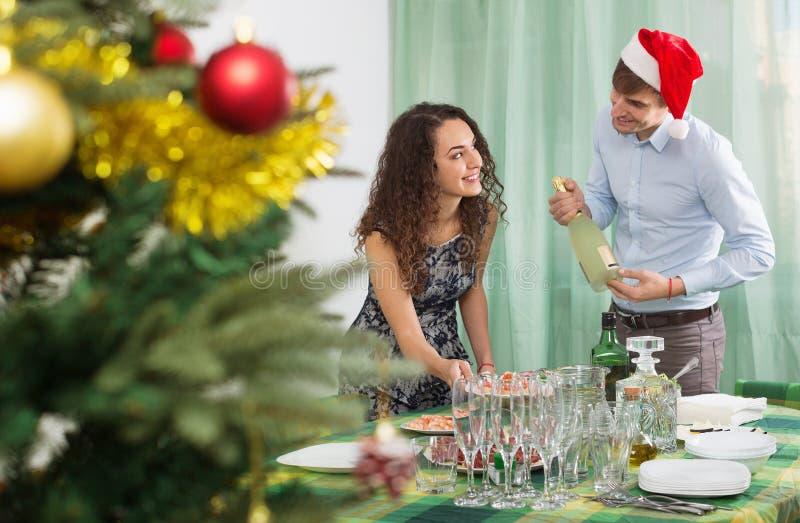 客人的愉快的人和女孩服务圣诞节桌 免版税库存照片