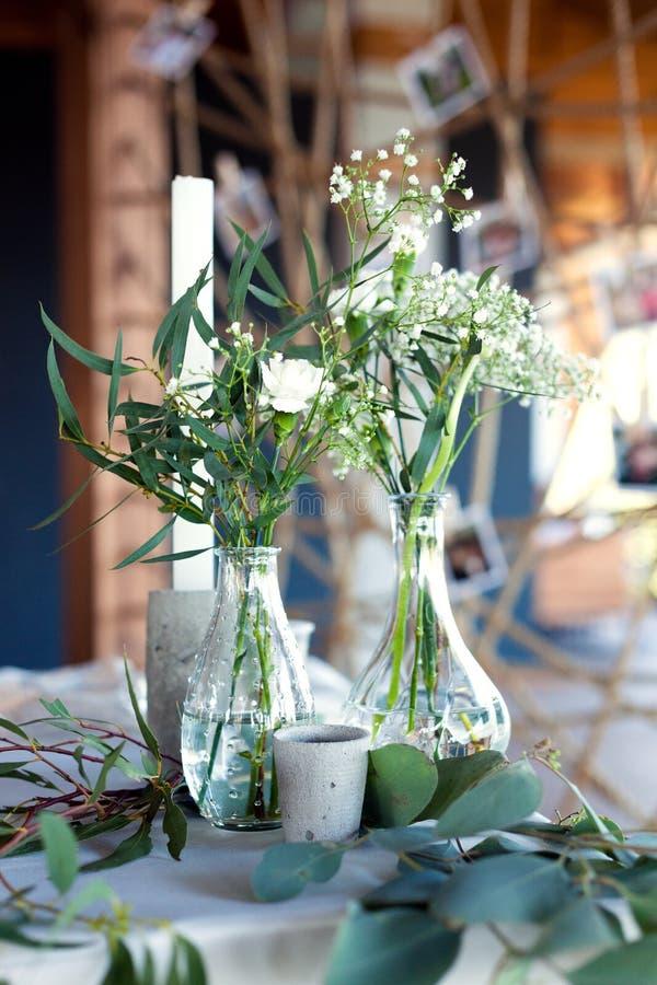 客人的表,盖用桌布,装饰用蜡烛,透明玻璃花瓶,鲜花和服务与刀匠 免版税库存图片