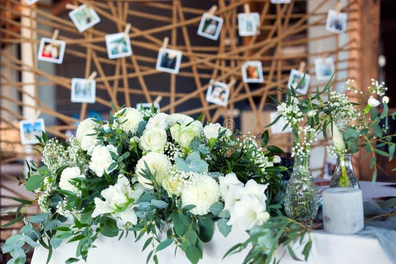客人的表,盖用桌布,装饰用蜡烛,透明玻璃花瓶,鲜花和服务与刀匠 库存照片