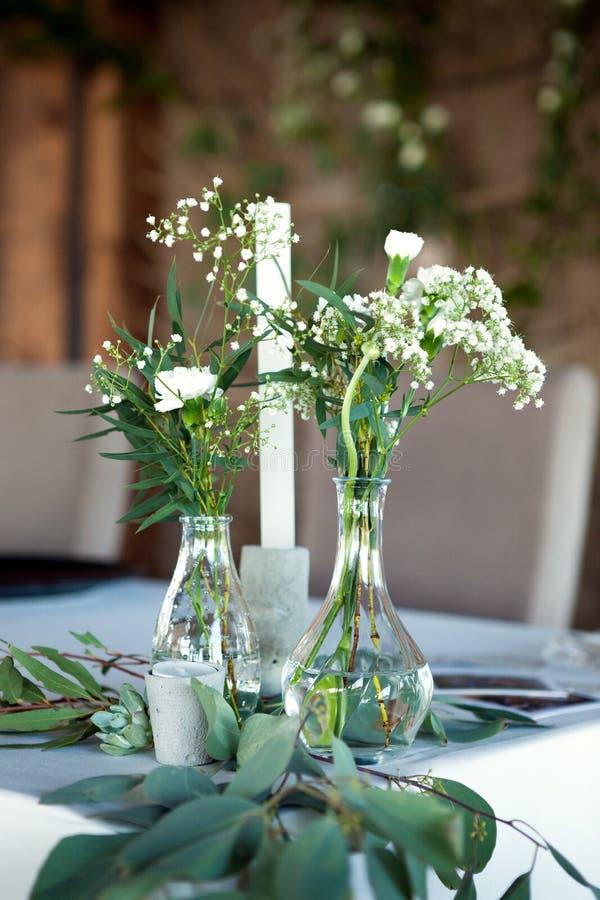 客人的表,盖用桌布,装饰用蜡烛,透明玻璃花瓶,鲜花和服务与刀匠 图库摄影
