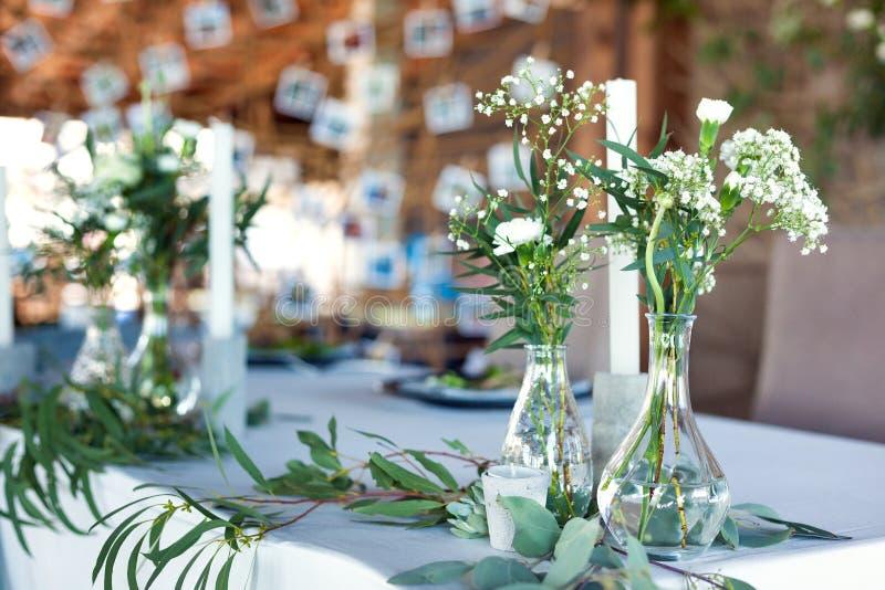 客人的表,盖用桌布,装饰用蜡烛,透明玻璃花瓶,鲜花和服务与刀匠 库存图片