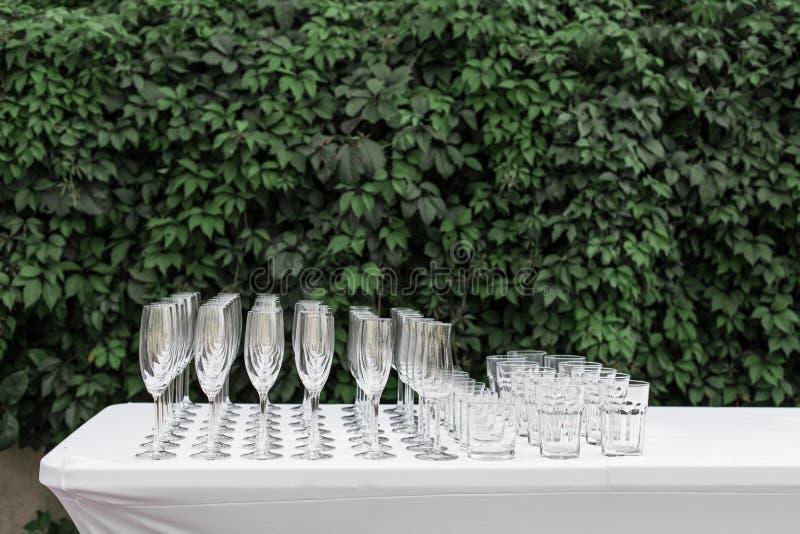 客人的许多空的干净的玻璃在自助餐欢乐婚姻的桌上 库存照片
