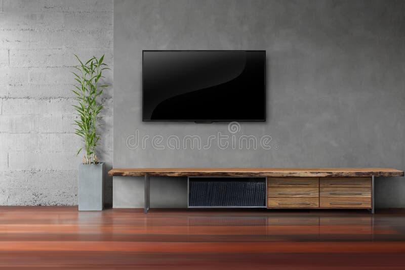 客厅带领了在混凝土墙上的电视有木桌的 图库摄影