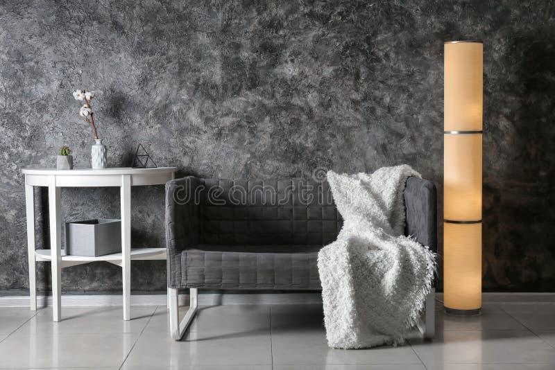 客厅现代内部有时髦的沙发、桌和灯的在黑暗的墙壁附近 免版税库存照片
