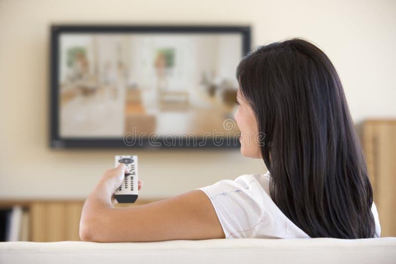 客厅电视注意的妇女 库存图片