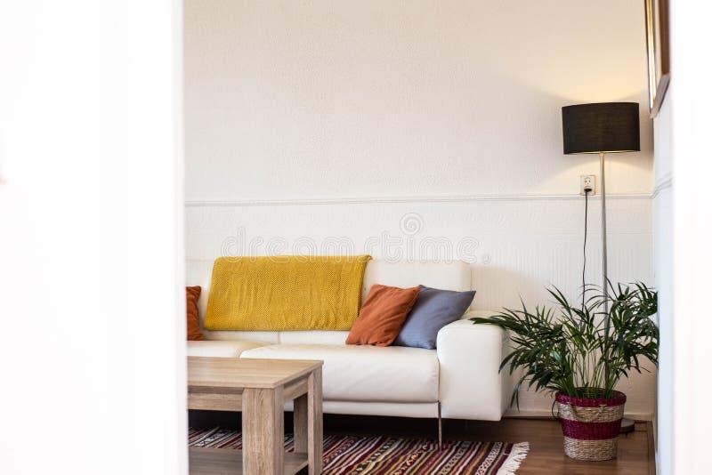 客厅简单,工业室内设计有站立在有黄色和蓝色坐垫的一个灰色沙发前面的木桌的 库存照片