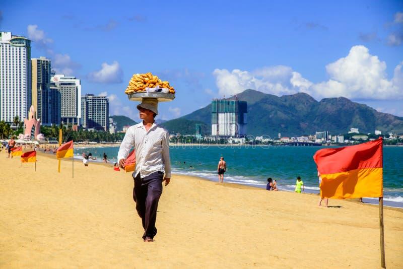 客商卖地方食物给海和山的海滩的游人 免版税库存图片