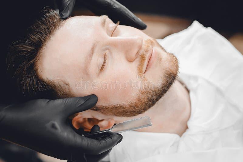 客户为皇家刮的剃刀理发店做准备 免版税库存图片