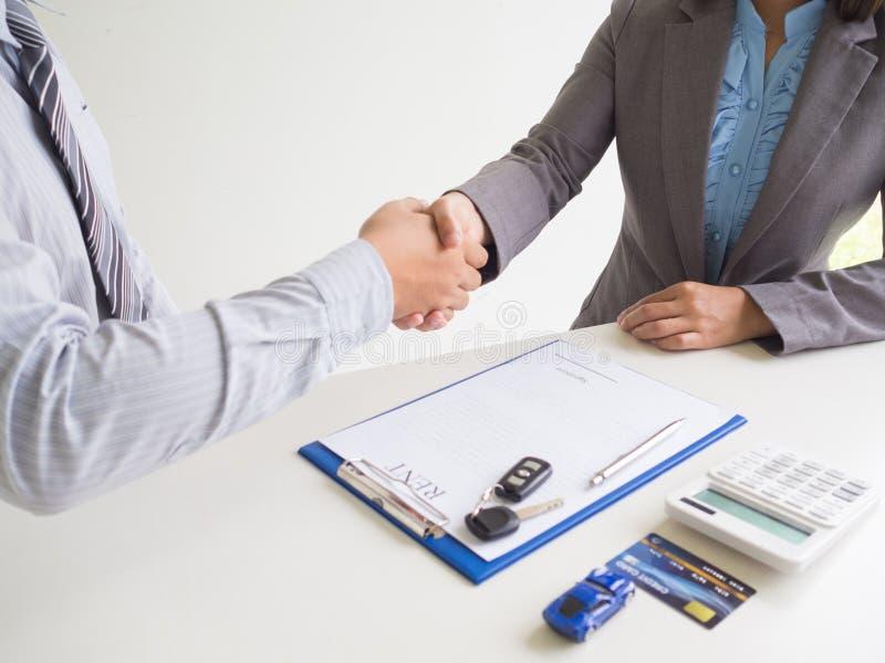 客户妇女使用信用卡并签名租车表销售员握手交易业务 免版税库存照片