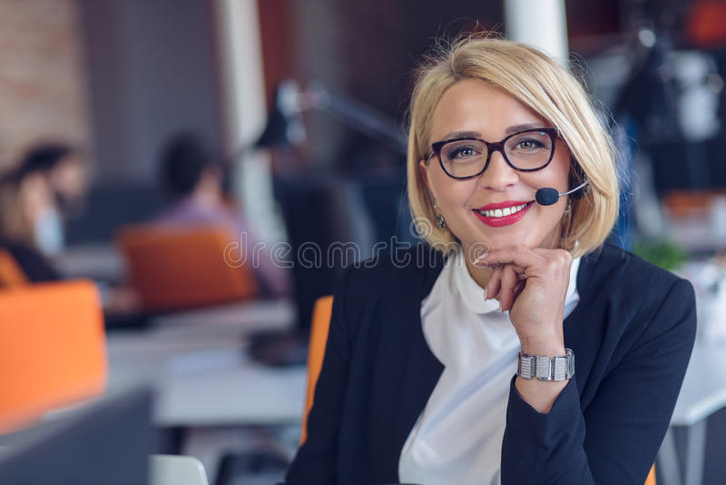 客户服务代表在工作 运转在计算机的耳机的美丽的少妇 免版税库存照片