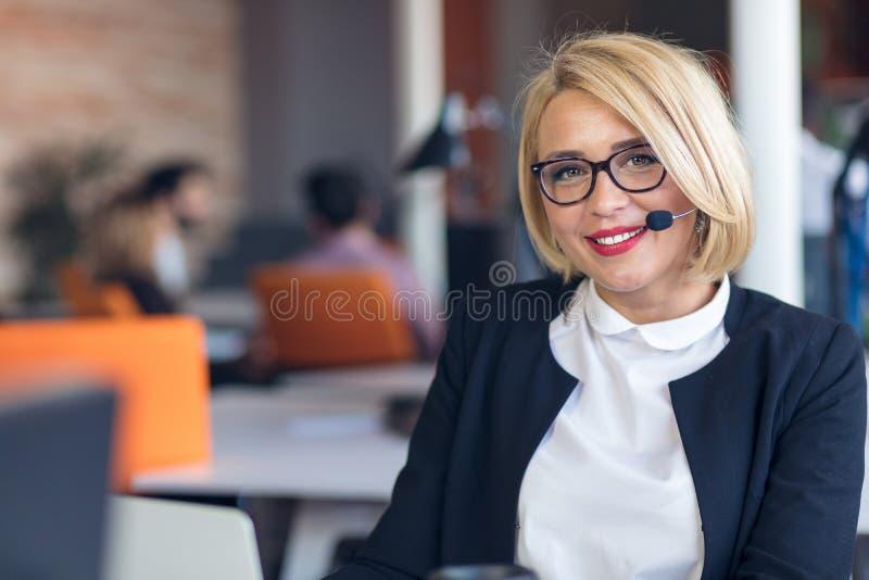 客户服务代表在工作 运转在计算机的耳机的美丽的少妇 免版税库存图片