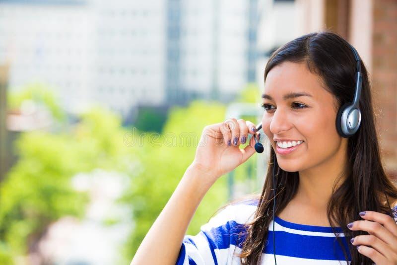 客户服务代表或电话中心代理或者支撑杆或者操作员有耳机的在外部阳台 免版税库存图片