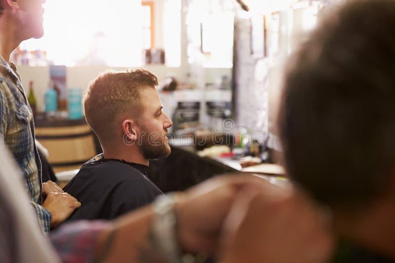 给客户理发的男性理发师在商店 免版税库存图片