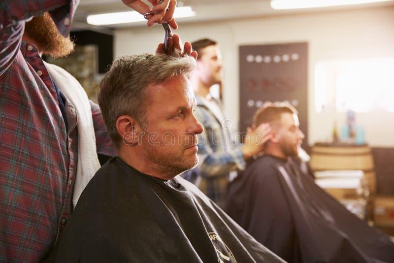给客户理发的男性理发师在商店 免版税图库摄影