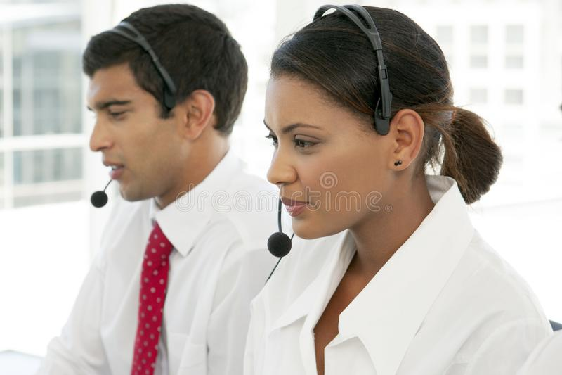 客服代表在工作在不同种族的电话中心 库存图片
