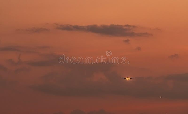 ?? 客机着陆在有美丽的日落天空和云彩的机场 到来飞行 飞机飞行 免版税图库摄影