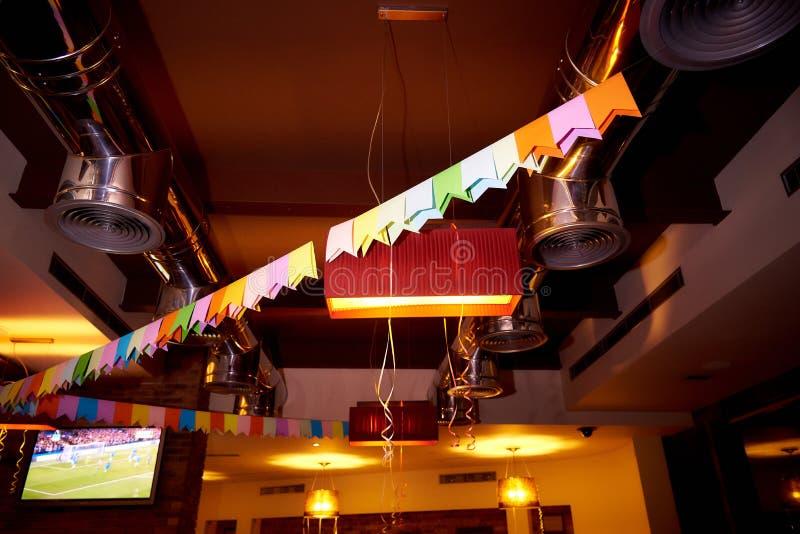 客栈的天花板用五颜六色的旗子和丝带装饰 免版税库存照片