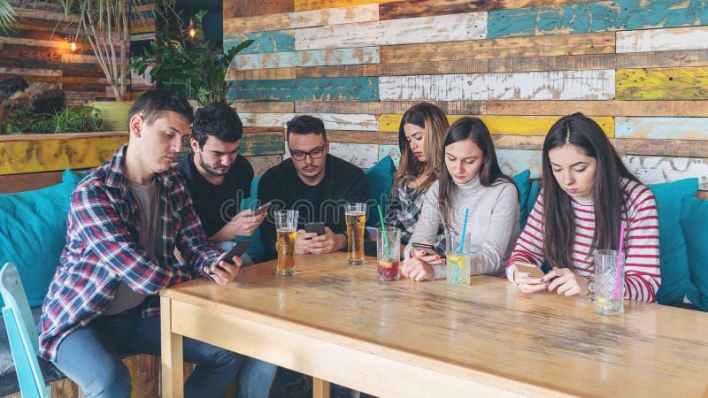 客栈的朋友忽略的小组倾向于手机 免版税库存图片