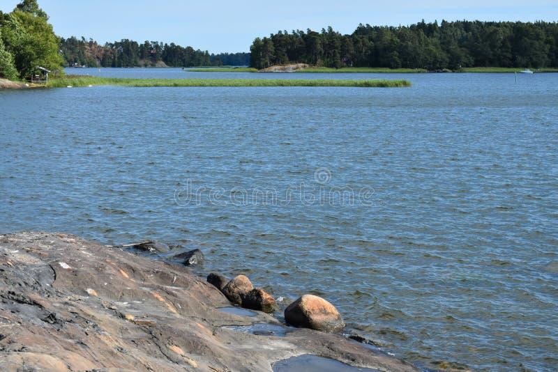 客舱和森林横跨一个岩石湖的岸 库存照片