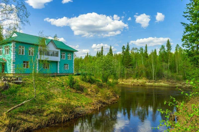 客舱在河的森林 免版税库存照片
