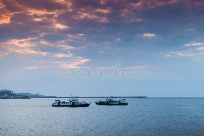 客船在五颜六色的晚上天空下 免版税库存图片