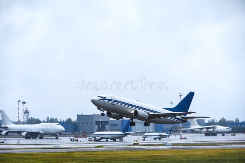 客轮离开入从机场跑道的天空与雨的多云天气的 免版税库存图片