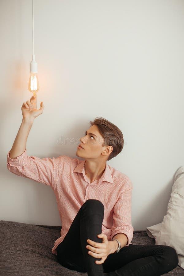 室内小条衬衣和黑牛仔裤坐的年轻可爱的人和使用与电灯泡 概念想法,想法 库存图片