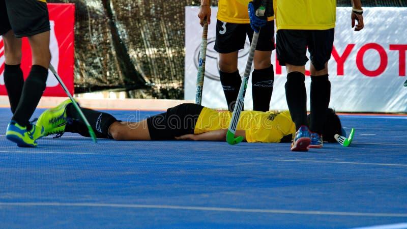 室内曲棍球 受伤的球员在地板上说谎 免版税库存图片