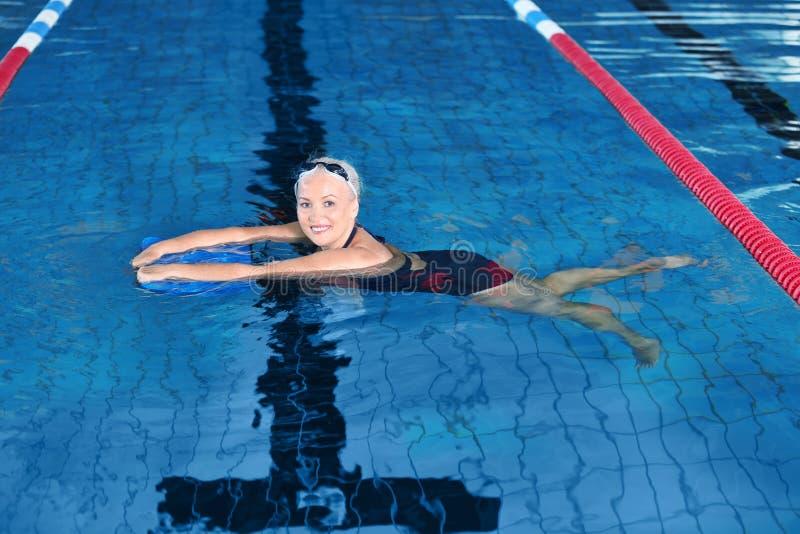室内游泳池的嬉戏资深妇女 图库摄影