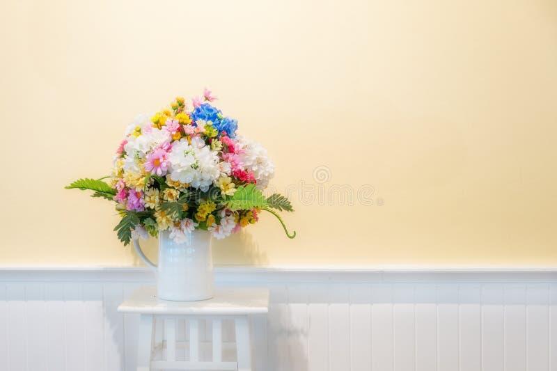 室内装璜的假花在与奶油色wa的白色木头 图库摄影