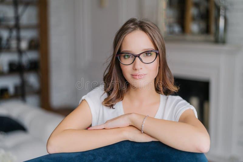 室内观点的眼镜的俏丽的妇女,保留手沙发,在客厅在家摆在,考虑某事, dres 免版税库存图片