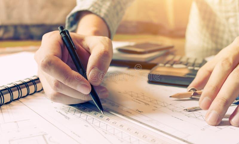 室内设计师或建筑师回顾的图纸和举行 免版税库存照片