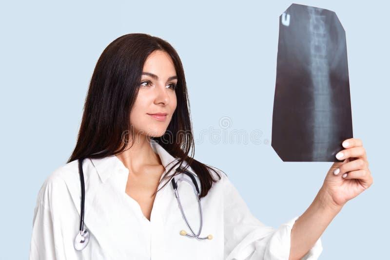 室内shotof宜人的看起来的女性护士或医生神色殷勤地和愉快地在X光芒,研究骨骼,在白色m穿戴了 库存图片